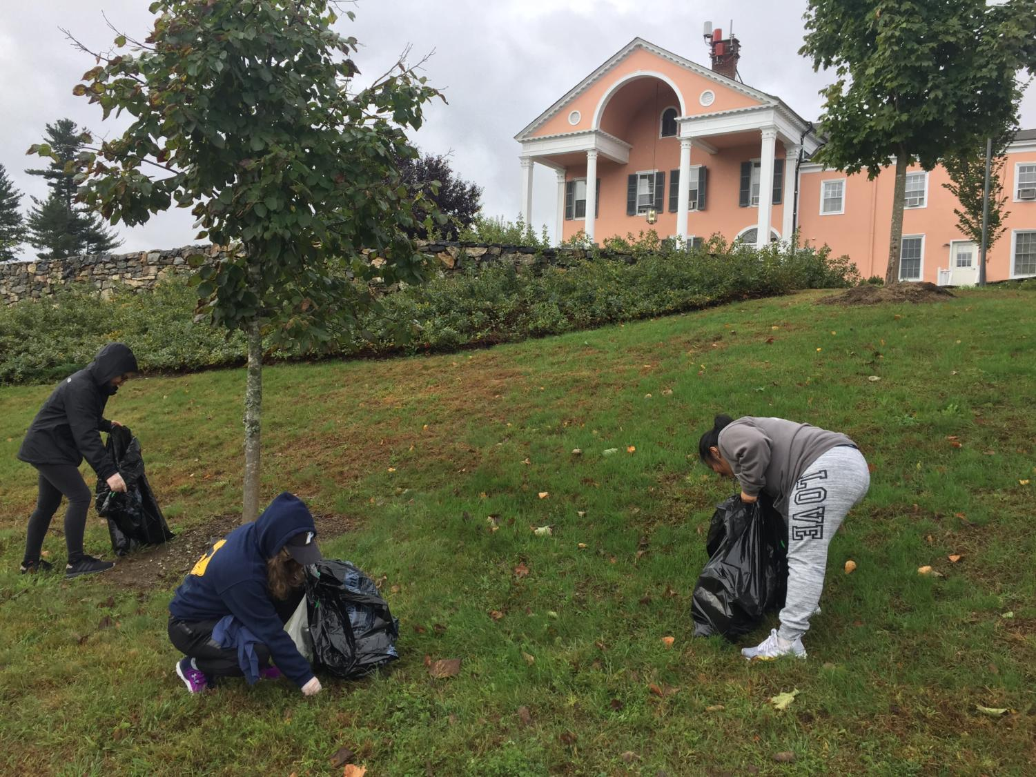 Three students are picking up trash on Choate hill during campus cleanup.
