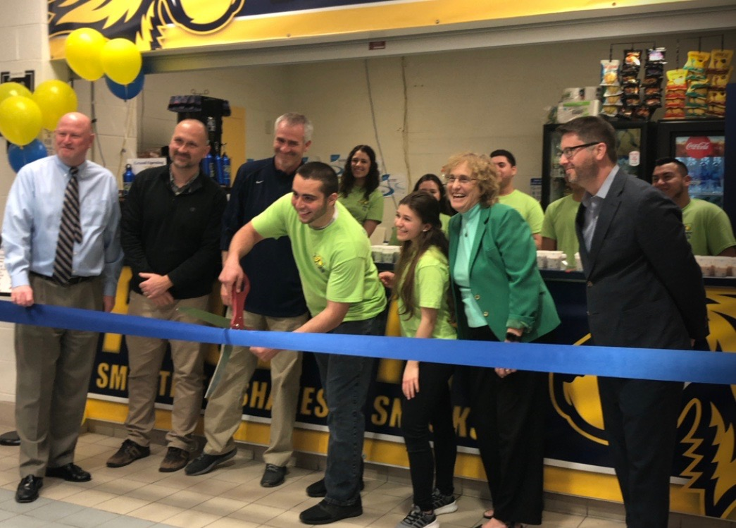Matthew Lasala cuts the ribbon to mark the official grand opening of PaceFit. Lasell was surrounded by  Nicole Forgione, his team of managers, Kathy Winsted and the athletics department.