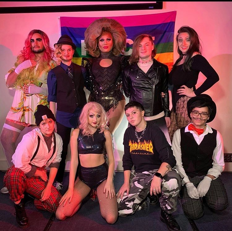 Drag Queen host Tess Tickles poses with the performers at