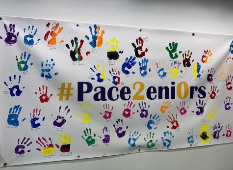 The 2020 banner displays colorful handprints of various seniors. The banner could be found in the entrance of Kessel.